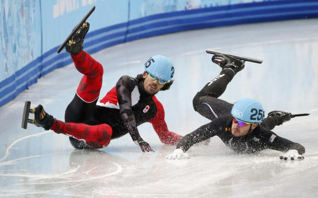 Canada's Charles Hamelin (L) and Eduardo Alvarez of the U.S. fall during the men's 1,000 metres short track speed skating quarter-finals race at the Iceberg Skating Palace at the Sochi 2014 Winter Olympics February 15, 2014. REUTERS/Lucy Nicholson (RUSSIA - Tags: SPORT SPEED SKATING OLYMPICS TPX IMAGES OF THE DAY) ATTENTION EDITORS: PICTURE 09 OF 20 FOR PACKAGE 'SOCHI - EDITOR'S CHOICE' TO FIND ALL SEARCH 'EDITOR'S CHOICE - 15 FEBRUARY 2014'