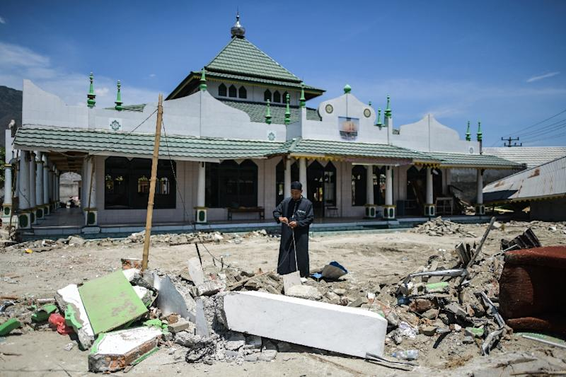 A week on from the disaster in Indonesia's Sulawesi some roads remain impassable, detritus is scattered everywhere and terrified people are sleeping outside for fear of further quakes (AFP Photo/MOHD RASFAN)