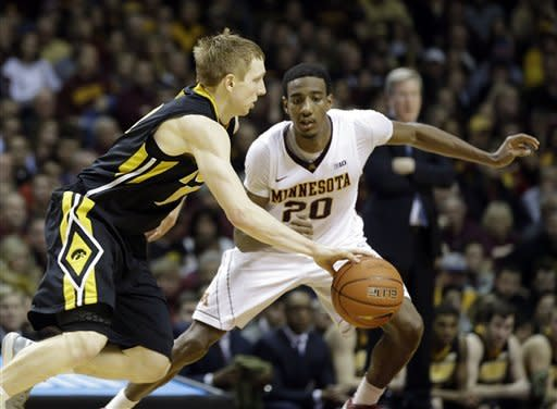 Iowa's Mike Gesell, left, drives by Minnesota's Austin Hollins in the first half of an NCAA college basketball game on Sunday, Feb. 3, 2013, in Minneapolis. Minnesota won 62-59. Gesell led Iowa, scoring with 11 points, while Hollins led Minnesota with 17. (AP Photo/Jim Mone)