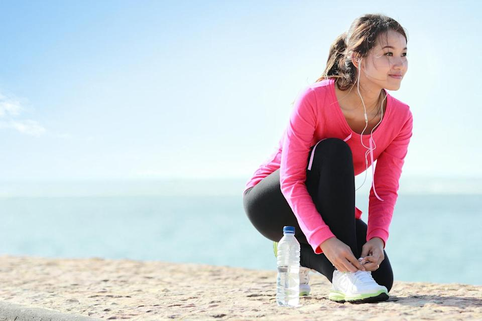 woman lacing her shoes before a workout