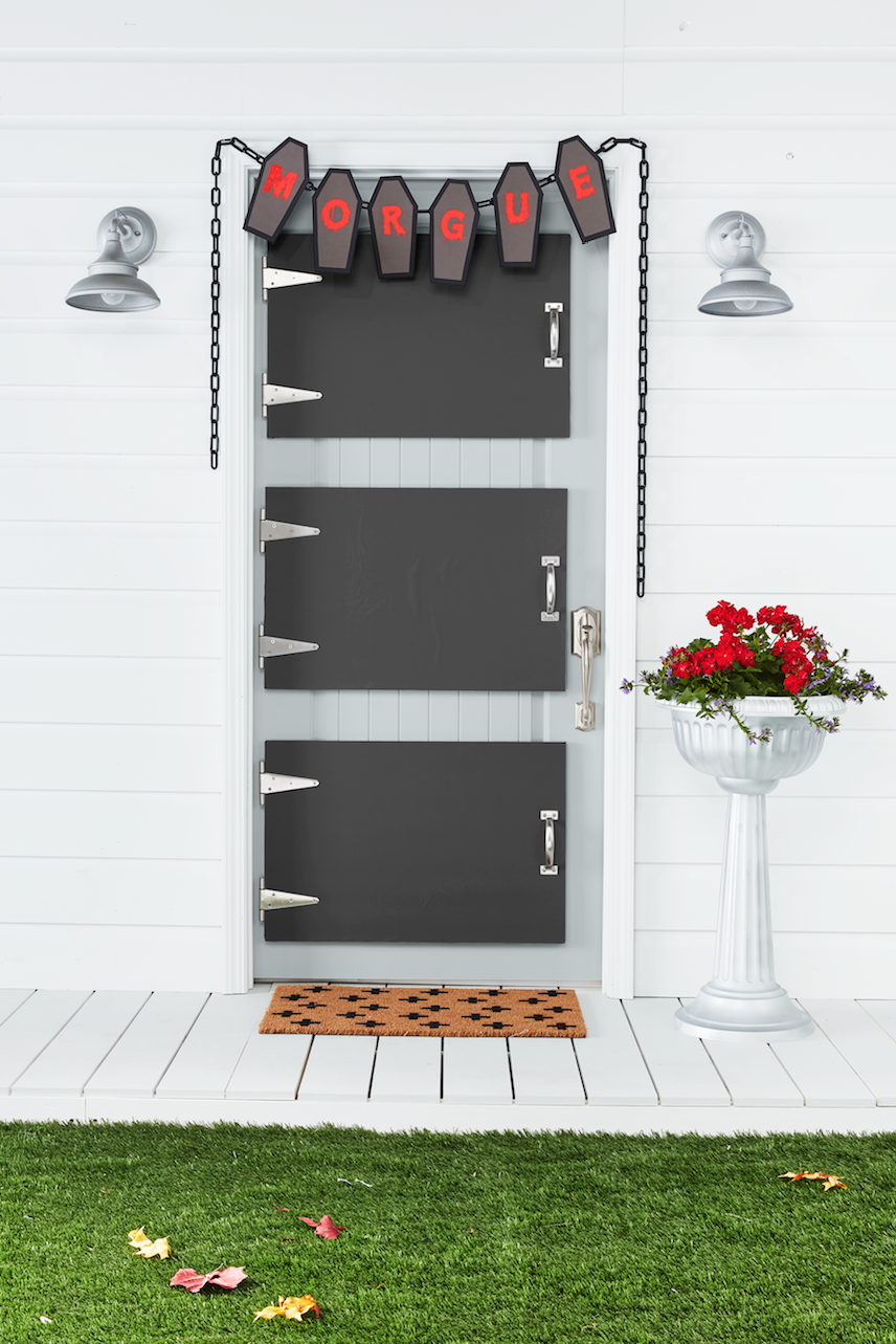 """<p>Front doors? More like """"morgue drawers."""" This creepy idea will have all the kids running for the hills—and then running back for some candy.</p><p><strong>Craft the Doors: </strong>Attach three precut 20- by 30-inch pieces of foam core together with spray adhesive. Attach a piece of black paper, cut to size, to the top piece of foam core using spray adhesive. Insert the rectangular piece of two 6-inch stainless steel T-hinges between the first and second pieces of foam core on one of the short sides; """"screw"""" in place. Place a 6 1/2-inch handle on the opposite side; """"screw"""" in place. Cover exposed edges of the foam core with silver duct tape, folding any excess to the back. Make two more doors. Adhere to house door with heavy-duty self-adhesive Velcro. Cut five coffin shapes from black and gray kraft paper. Paint letters on gray coffins with <a href=""""https://www.amazon.com/Apple-Barrel-Acrylic-Assorted-J20401/dp/B0018N6IPY?tag=syn-yahoo-20&ascsubtag=%5Bartid%7C10050.g.1370%5Bsrc%7Cyahoo-us"""" rel=""""nofollow noopener"""" target=""""_blank"""" data-ylk=""""slk:red acrylic paint"""" class=""""link rapid-noclick-resp"""">red acrylic paint</a> to spell """"morgue"""" and attach to black coffins with double-sided tape. Hang a plastic chain above the door and attach coffin cutouts with hot-glue. </p>"""