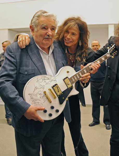 ALTERNATIVE CROP OF EDB102 - In this picture released by Uruguay's Press Office, President Jose Mujica, left, poses with Aerosmith's Steven Tyler after receiving an autographed guitar as a gift at the presidential house in Montevideo, Uruguay, Tuesday, Oct. 8, 2013. The band will perform Wednesday as part of their Latin America tour. (AP Photo/Uruguay Press Office, Alvaro Salas)