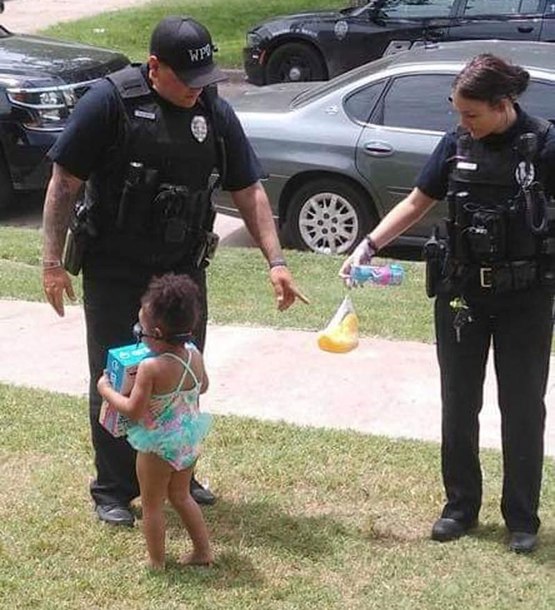 Two Wichita police officers are pictured speaking with a little girl in her togs. They found out she was playing in the dirt because the pool was closed.
