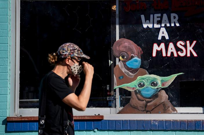 A woman passes a sign advising people to wear their masks outside Amy's Ice Creams in Austin, Texas.