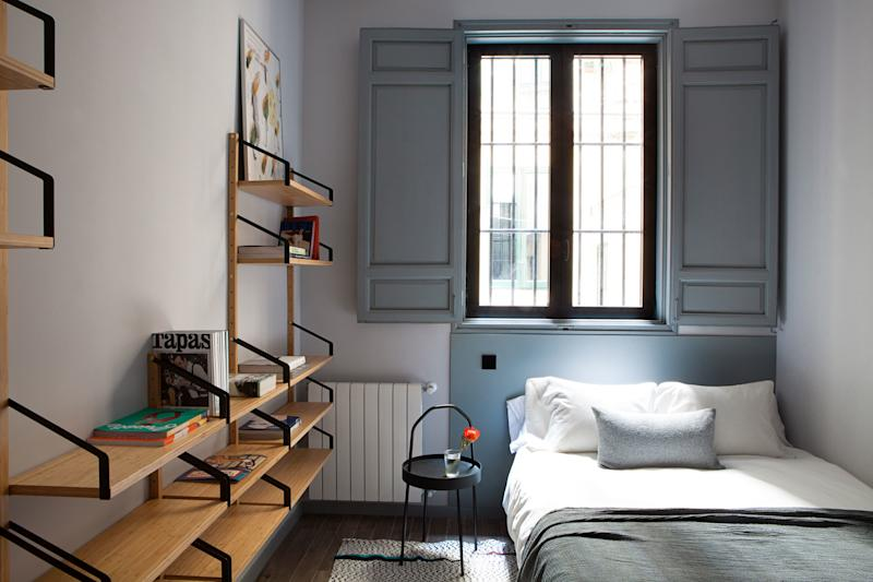 """After: Ana and Enrique took a whole different approach in the last bedroom, called the """"Wooden Room""""; there's no in-your-face color here. Instead, everything that's not warm wood is a soft greenish-gray, in an attempt to make the shadowy space (it faces a courtyard) as welcoming as possible."""