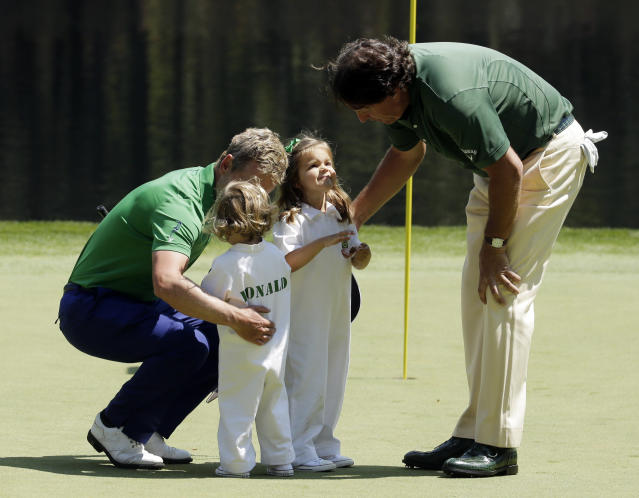 Phil Mickelson, right, talks to Luke Donald, of England's daughters Sophie and Elle during the par three competition at the Masters golf tournament Wednesday, April 9, 2014, in Augusta, Ga. (AP Photo/Chris Carlson)