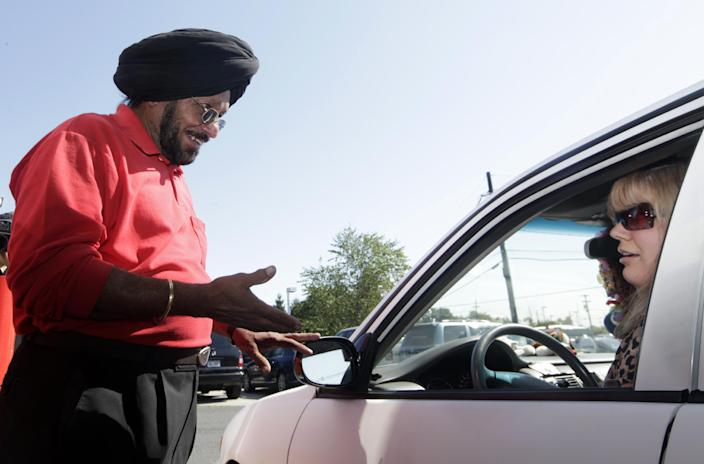 Lukoil service station worker Harbhasan Singh explains Wednesday, Sept. 12, 2012, in South Plainfield, N.J., to regular customer Tiffany Price that as a protest to what they say are unfair pricing practices by Lukoil North America, the station has raised their gas price to more than $8 a gallon. Price still bought gas in support of the protest. More than 50 Lukoil gas stations in New Jersey and Pennsylvania were jacking up prices to more than $8 a gallon Wednesday to protest what they say are unfair pricing practices by Lukoil North America that they say leave them at a competitive disadvantage. (AP Photo/Mel Evans)