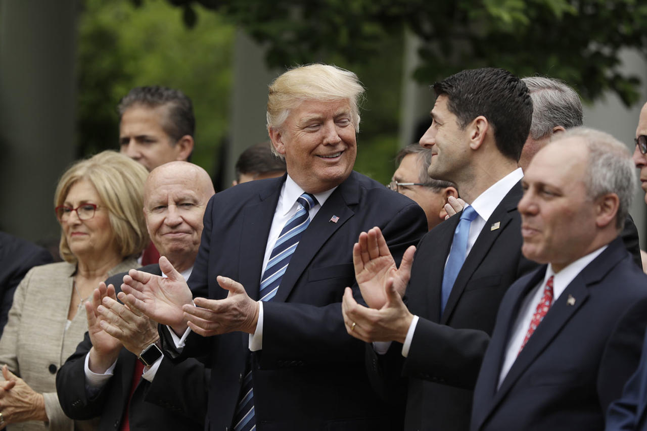 <p>President Trump, flanked by House Ways and Means Committee Chair Kevin Brady and House Speaker Paul Ryan applaud at the White House on May 4, 2017, after the House pushed through a health care bill. (Photo: Evan Vucci/AP) </p>