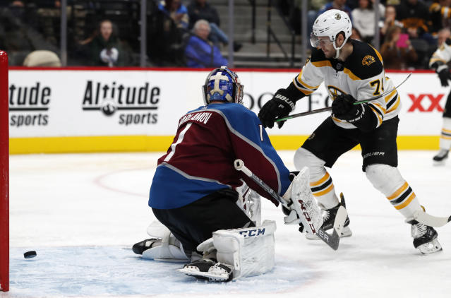 Boston Bruins left wing Jake DeBrusk, right, watches his shot for a goal against Colorado Avalanche goaltender Semyon Varlamov during the second period of an NHL hockey game Wednesday, Nov. 14, 2018, in Denver. (AP Photo/David Zalubowski)
