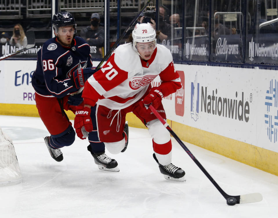 Detroit Red Wings defenseman Troy Stecher, right, controls the puck in front of Columbus Blue Jackets forward Jack Roslovic during the second period of an NHL hockey game in Columbus, Ohio, Saturday, May 8, 2021. (AP Photo/Paul Vernon)