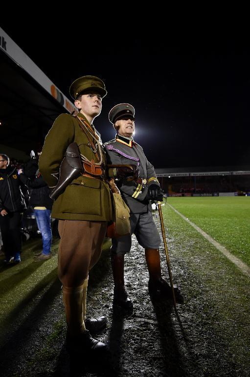 """People in military WWI uniforms watch the """"Game of Truce"""", a recreation of a First World War Christmas truce football match, in Aldershot, west of London, on December 17, 2014 (AFP Photo/Ben Stansall )"""