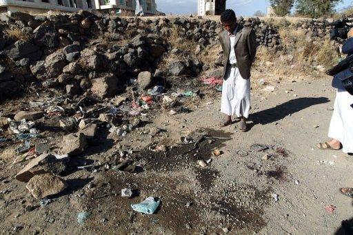 Men inspect the site where a Saudi diplomat and his bodyguard were killed in Sanaa's southern district of Hada