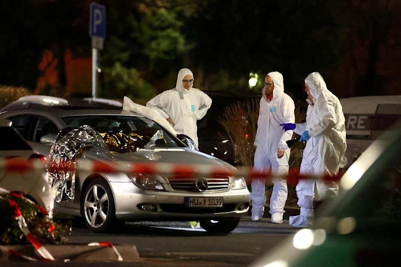 Forensic experts work around a damaged car after a shooting in Hanau: REUTERS