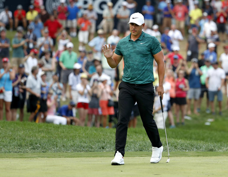 Brooks Koepka waves to the crowd after making his birdie putt on the 15th hole during the final round of the PGA Championship golf tournament at Bellerive Country Club, Sunday, Aug. 12, 2018, in St. Louis. (AP Photo/Jeff Roberson)
