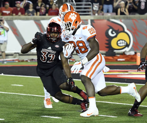 "Clemson's Tavien Feaster (28) runs from the defense of Louisville's <a class=""link rapid-noclick-resp"" href=""/ncaaf/players/227575/"" data-ylk=""slk:Stacy Thomas"">Stacy Thomas</a>. (AP Photo/Timothy D. Easley)"