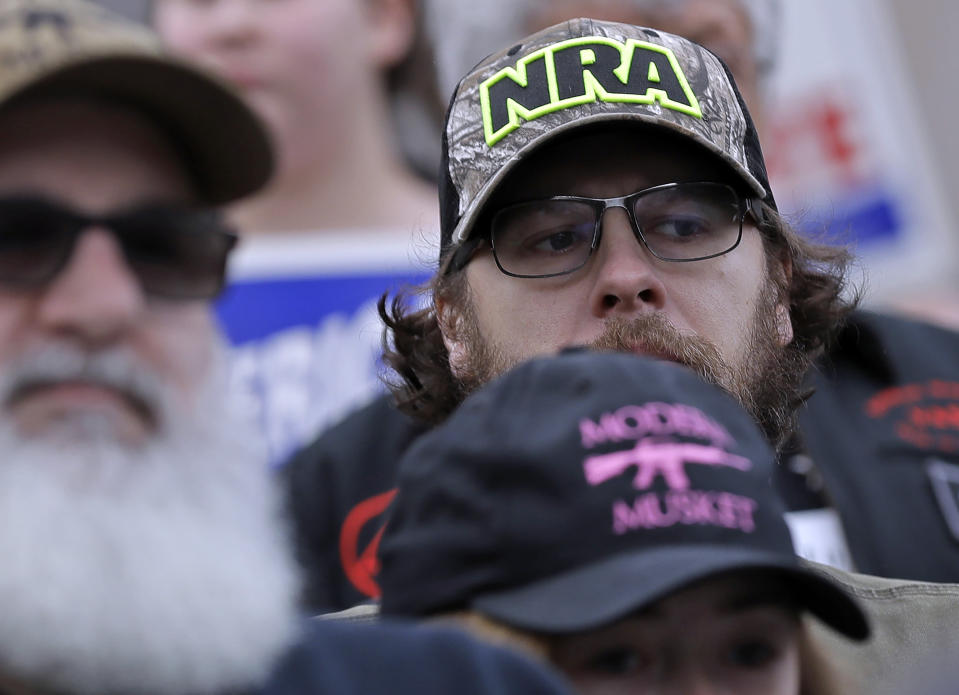 FILE — In this Jan. 18, 2019, file photo, an attendee at a gun-rights rally wears a hat supporting the National Rifle Association, at the Capitol in Olympia, Wash. A New York judge on Thursday, Jan. 21, 2021, denied the National Rifle Association's bid to throw out a state lawsuit that seeks to put the powerful gun advocacy group out of business. (AP Photo/Ted S. Warren, File)