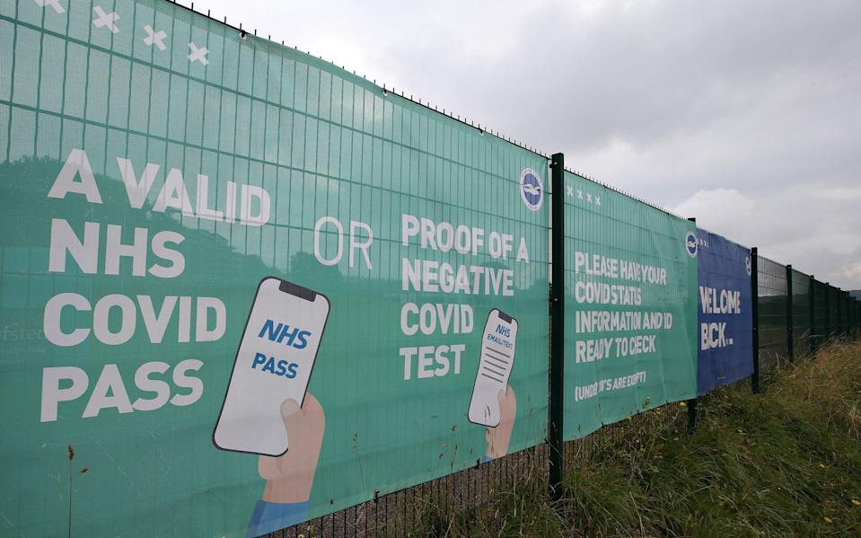 NHS Covid Pass and Negative Covid test advice is seen on a banner outside the stadium prior to the Premier League match between Brighton & Hove Albion and Watford at American Express Community Stadium on August 21, 2021 in Brighton, England - GETTY IMAGES