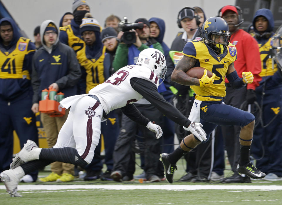 West Virginia wide receiver Mario Alford (5) gets past Texas A&M defensive back Armani Watts as Alford scores a touchdown on a 45-yard pass reception against Texas A&M in the first half of the Liberty Bowl NCAA college football game, Monday, Dec. 29, 2014, in Memphis, Tenn. (AP Photo/Mark Humphrey)