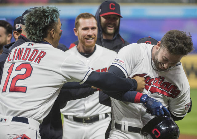 Cleveland Indians' Tyler Naquin, right, is mobbed by Francisco Lindor and Jordan Luplow after hitting a winning RBI-single off Seattle Mariners relief pitcher Anthony Swarzak in the ninth inning of a baseball game in Cleveland, Friday, May 3, 2019. (AP Photo/Phil Long)