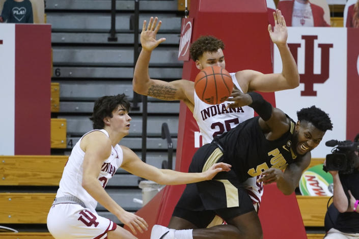 Purdue's Trevion Williams (50) passes the ball away from Indiana's Race Thompson (25) and Trey Galloway (32) during the second half of an NCAA college basketball game Thursday, Jan. 14, 2021, in Bloomington, Ind. Purdue won 81-69. (AP Photo/Darron Cummings)