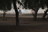 In this Wednesday, April 15, 2020 photograph, a laborer walks past graffiti showing Marxist icon Che Guevara, a hammer and sickle and a portrait of Dubai ruler Sheikh Mohammed bin Rashid Al Maktoum in the Al Quoz neighborhood of Dubai, United Arab Emirates. Migrant workers in oil-rich Gulf Arab states find themselves trapped by the coronavirus pandemic. They are losing jobs, running out of money and desperate to return home as the coronavirus, stalks their labor camps. An unknown number of workers have contracted the virus or have suddenly been forced into mass quarantines, leaving them exposed and painfully vulnerable with little recourse for help. (AP Photo/Jon Gambrell)