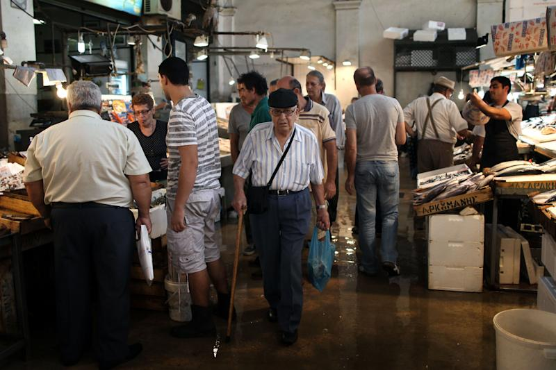 FILE In this Monday, Sept. 24, file photo an elderly man walks inside the Athens' central fish market. To the casual visitor, all might appear well in Athens. But scratch the surface and you find a society in freefall, ripped apart by the most vicious financial crisis the country has seen in half a century. (AP Photo/Petros Giannakouris)
