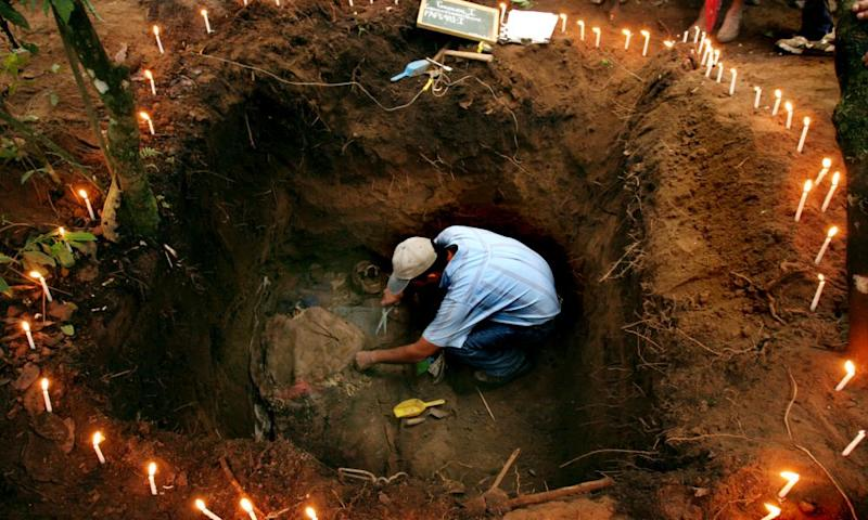 A forensic anthropologist works to exhume a body of a poor farmer killed by the Guatemalan army in 1982 during the country's civil war, in Chucalibal, Quiché