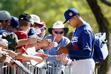 Julio Urias signs autographs for fans following a spring training workout Saturday. (Getty)