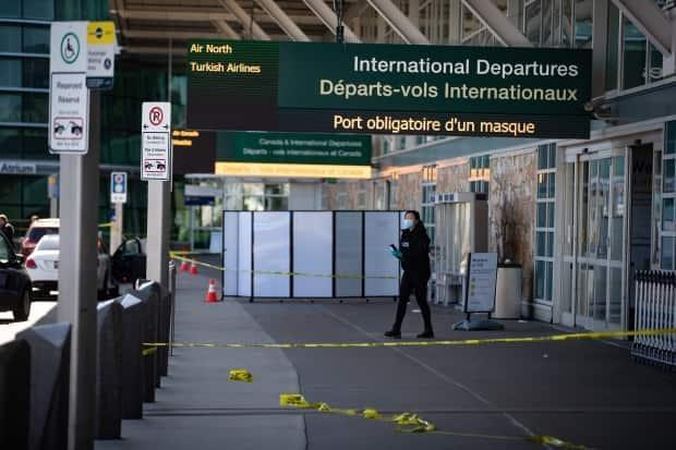 An RCMP officer works at the scene after a shooting at Vancouver International Airport on Sunday.