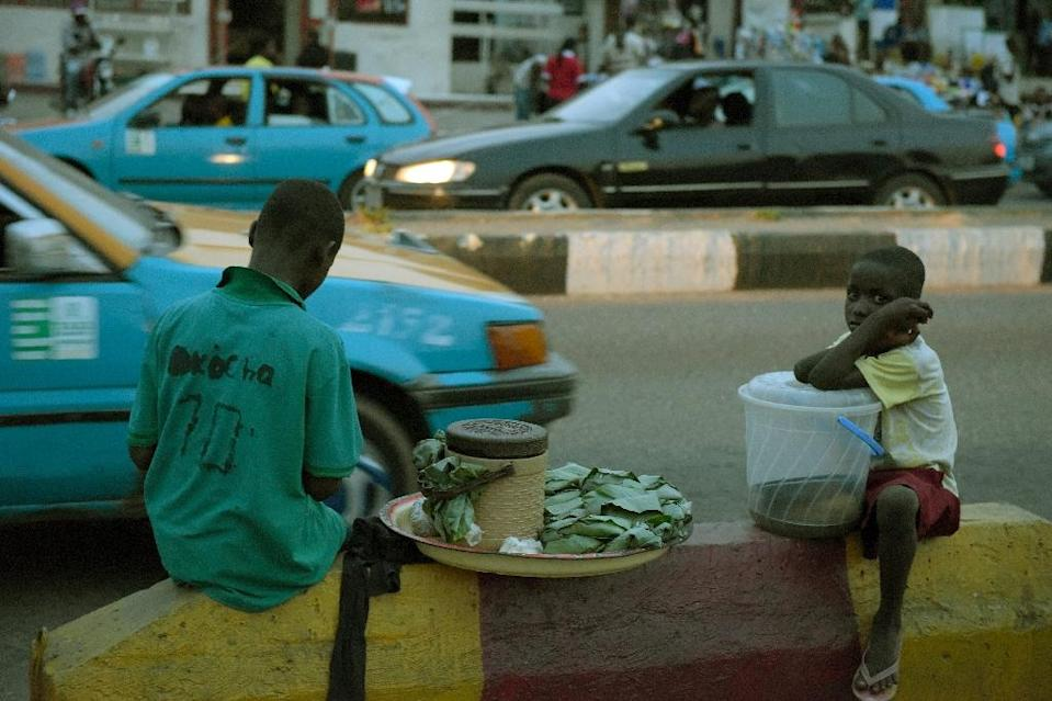 Two children sit on the pavement along the road at night to hawk their wares in Akure, southwestern Nigeria, on March 24, 2015 (AFP Photo/Pius Utomi Ekpei)