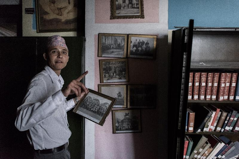 An employee looks at framed photographs alongside damaged book shelves at the Kaiser Library in Kathmandu on May 7, 2015 (AFP Photo/Philippe Lopez)
