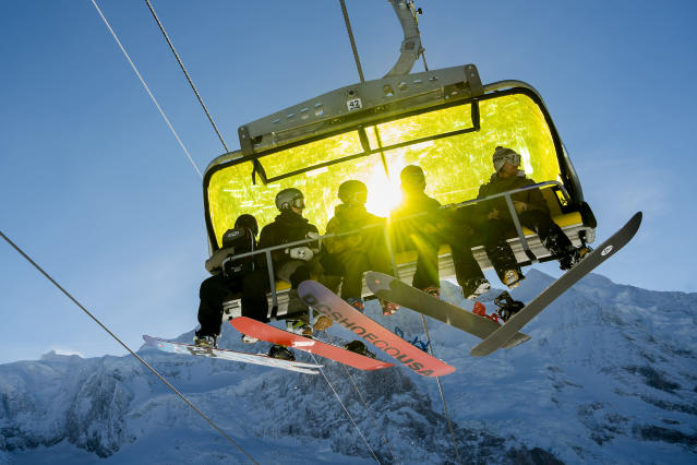 Skiers sit in a chairlift during a sunny winter day in front of the Jungfraujoch, in Wengen, Switzerland, Tuesday, Jan. 15, 2019. (Jean-Christophe Bott/Keystone via AP)