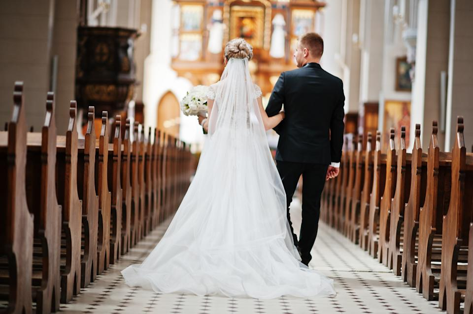 Rear shot of a stylish bride and father walk down the aisle of a grand catholic church.