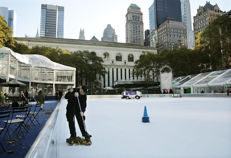 Debris is swept from the ice skating rink at Bryant Park in New York, Sunday, Nov. 10, 2013. A shooting at the ice rink at the popular midtown Manhattan park late Saturday sent two men to the hospital with non-life-threatening injuries, police said. (AP Photo/Peter Morgan)