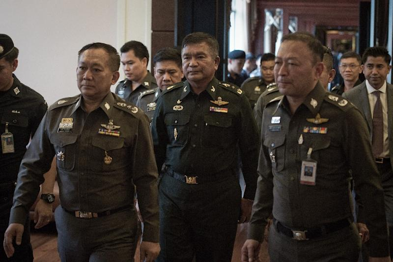 Thai Army Lieutenant General Manas Kongpan (centre) is surrounded by police officers as he turns himself in at the police headquarters in Bangkok on June 3, 2015