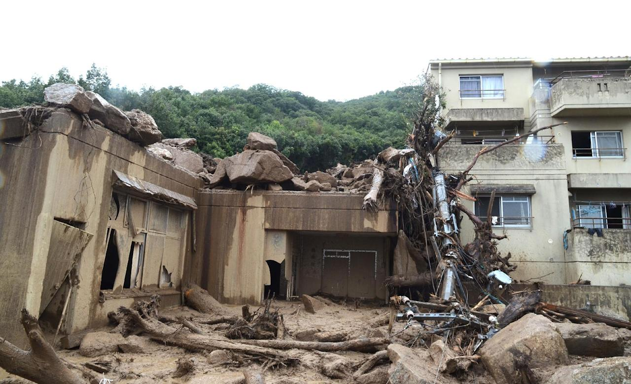 Big rocks sit on the roof of a severely damaged apartment building in a mud-covered residential area following a massive landslide in Hiroshima, western Japan, Friday, Aug. 22, 2014. Heavy rain showers forecast are raising the risks of further landslides in Hiroshima, hindering efforts to locate the dozens of people missing after hills in several areas collapsed earlier this week. (AP Photo/Kyodo News) JAPAN OUT