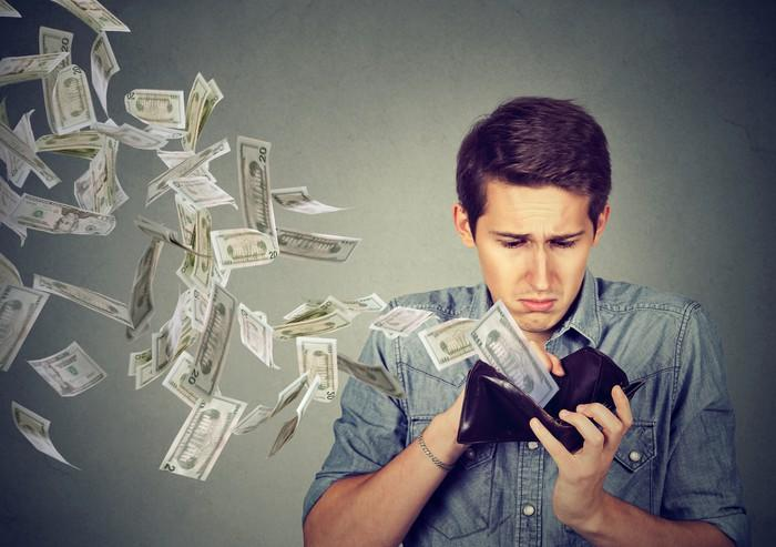 Man looking unhappy as money flies out of his wallet.