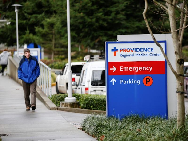 A man walks by the Providence Regional Medical Center campus after coronavirus victim treated in Everett