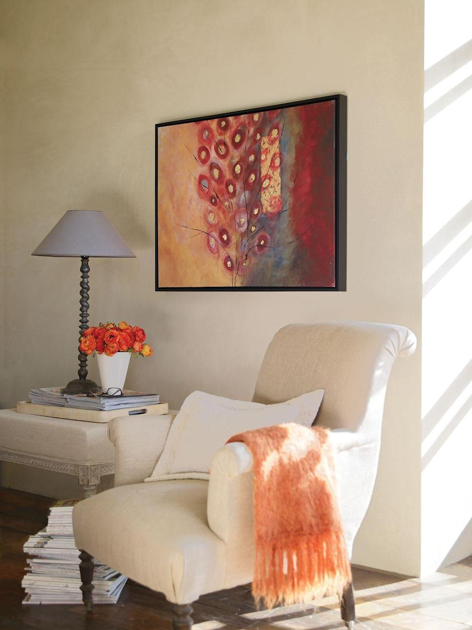 <p>A neutral chair is enlivened with an orange throw, which echoes the hues featured in the large-scale painting.</p>