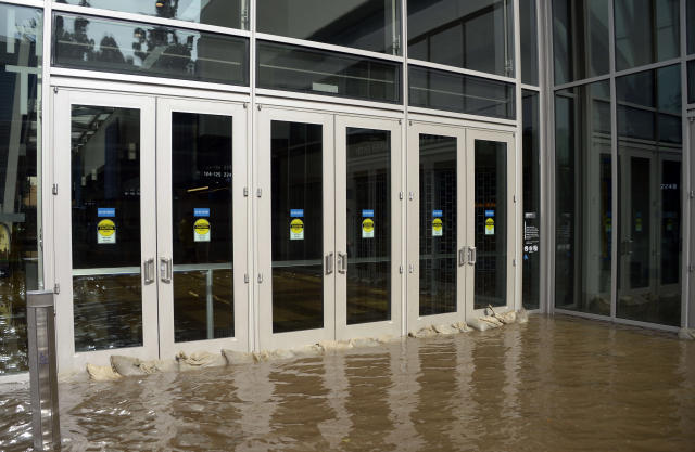 Sandbags fail to stop water from entering the main doors of Pauley Pavilion, home of UCLA basketball, on the UCLA campus after flooding from a broken 30-inch water main under nearby Sunset Boulevard inundated a large area of the campus in the Westwood section of Los Angeles, Tuesday, July 29, 2014. The 30-inch (75-centimeter) 93-year-old pipe that broke made a raging river of the street and sent millions of gallons (liters) of water across the school's athletic facilities, including the famed floor of Pauley Pavilion, the neighboring Wooden Center and the Los Angeles Tennis Center, and a pair of parking structures that took the brunt of the damage. (AP Photo/Mike Meadows)