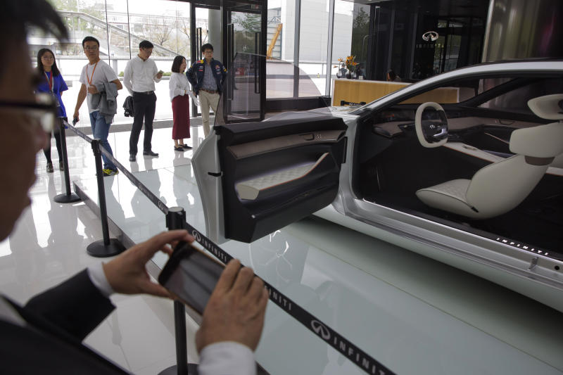 In this April 19, 2018, photo, visitors look at the Infiniti electric concept sedan at a showroom ahead of the Auto China 2018 to be held in Beijing, China. Auto China 2018, the biggest global auto show of the year, showcases China's ambitions to become a leader in electric cars and the industry's multibillion-dollar scramble to roll out models that appeal to price-conscious but demanding Chinese drivers. (AP Photo/Ng Han Guan)