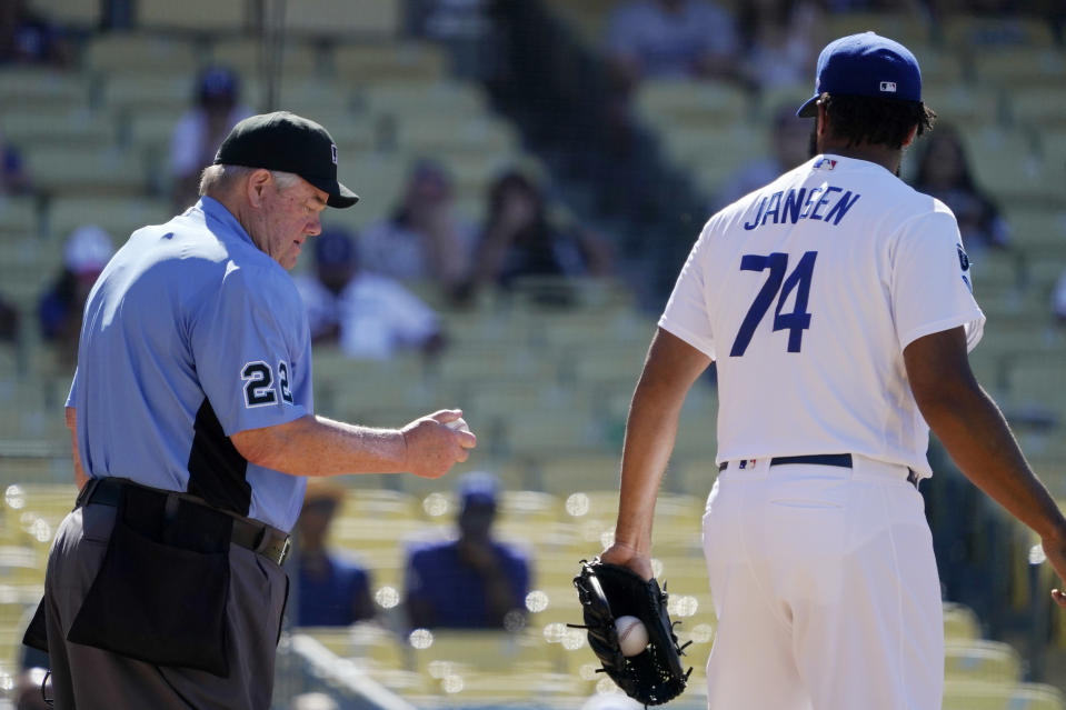 In this Sunday, June 13, 2021, photo, home plate umpire Joe West, left, takes a look at the ball that Los Angeles Dodgers relief pitcher Kenley Jansen had been using after giving him a fresh one during the ninth inning of a baseball game between the Dodgers and the Texas Rangers in Los Angeles. Pitchers will be ejected and suspended for 10 games for using illegal foreign substances to doctor baseballs in a crackdown by Major League Baseball that will start June 21. (AP Photo/Mark J. Terrill, File)