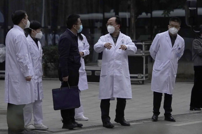 Chinese medical staff react as the World Health Organization team leave after their visit to the Hubei Provincial Hospital of Integrated Chinese and Western Medicine also know as the Hubei Province Xinhua Hospital in Wuhan in central China's Hubei province on Friday, Jan. 29, 2021. The World Health Organization team on Friday visited the hospital where China says the first COVID-19 patients were treated more than a year ago as part of the experts' long-awaited fact-finding mission on the origins of the coronavirus. (AP Photo/Ng Han Guan)