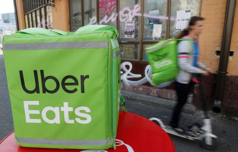 FILE PHOTO: An Uber Eats courier rides a scooter in Kiev
