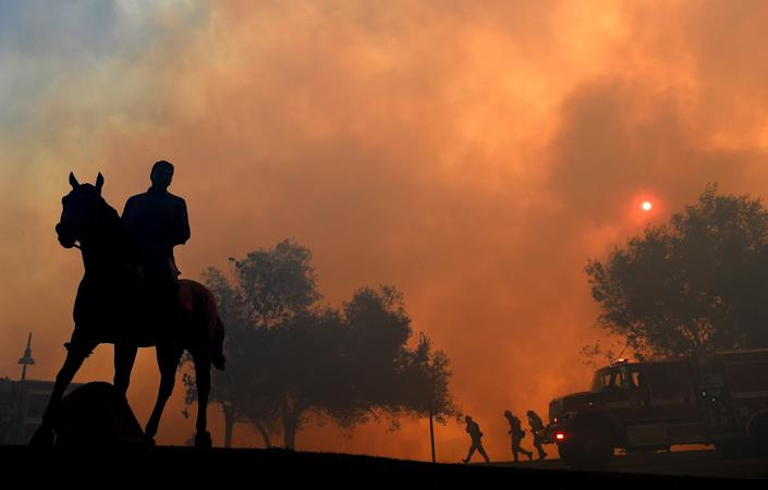 """A statue of former U.S. President Ronald Reagan titled """"Along The Trail"""" stands outside the Reagan Presidential Library as the Easy Fire burns on Oct. 30, 2019 in Simi Valley, California. (Photo by Wally Skalij/Los Angeles Times via Getty Images)"""