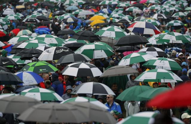 Patrons stand amid a sea of umbrellas as rain falls during third round play of the 2018 Masters golf tournament at the Augusta National Golf Club in Augusta, Georgia, U.S. April 7, 2018. REUTERS/Brian Snyder