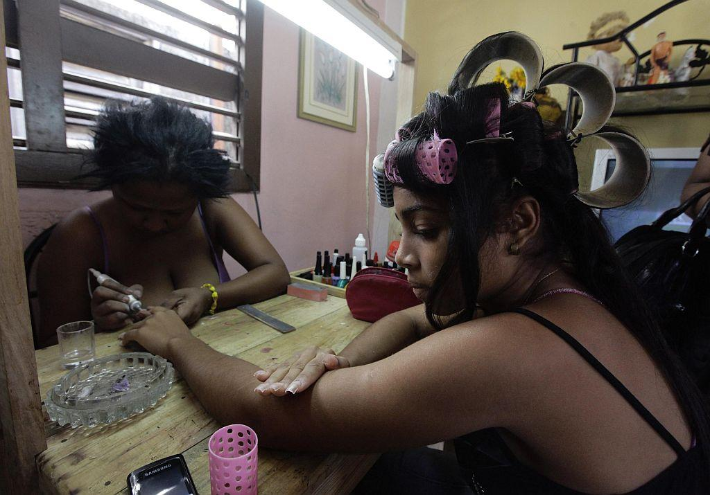 <p>Carmen Gonzalez (R) has her nails manicured as she prepares for her quinceanera.</p>