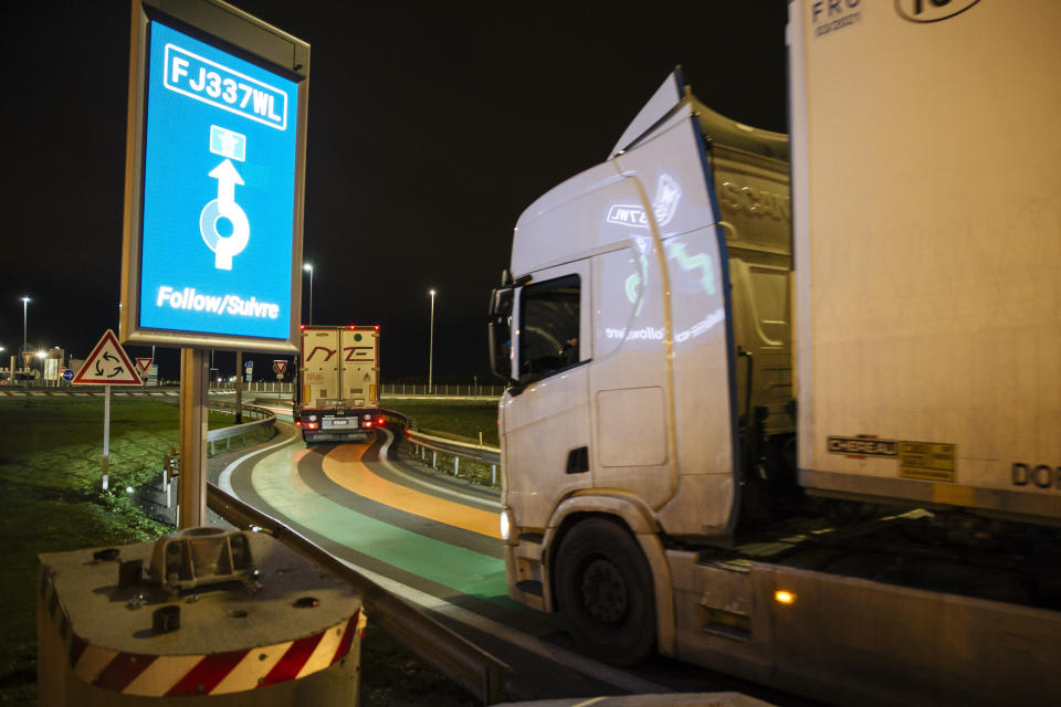 "A truck from Britain drives over green and orange lines on the road that is part of the new ""smart border"" customs infrastructure to enter France at the Eurotunnel terminal Friday, Jan. 1, 2021 in Coquelles, northern France. Eleven months after Britain's formal departure from the EU, Brexit becomes a fact of daily life on Friday, once a transition period ends and the U.K. fully leaves the world's most powerful trading bloc.(AP Photo/Lewis Joly)"