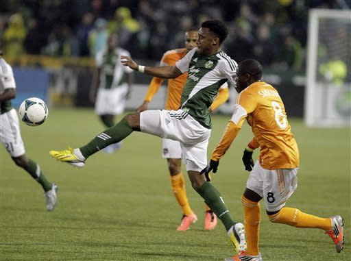 Portland Timbers forward Rodney Wallace, center, and Houston Dynamo defender Kofi Sardokie, right, chase down the ball during the first half of an MLS soccer game in Portland, Ore., Saturday, April 6, 2013. (AP Photo/Don Ryan)