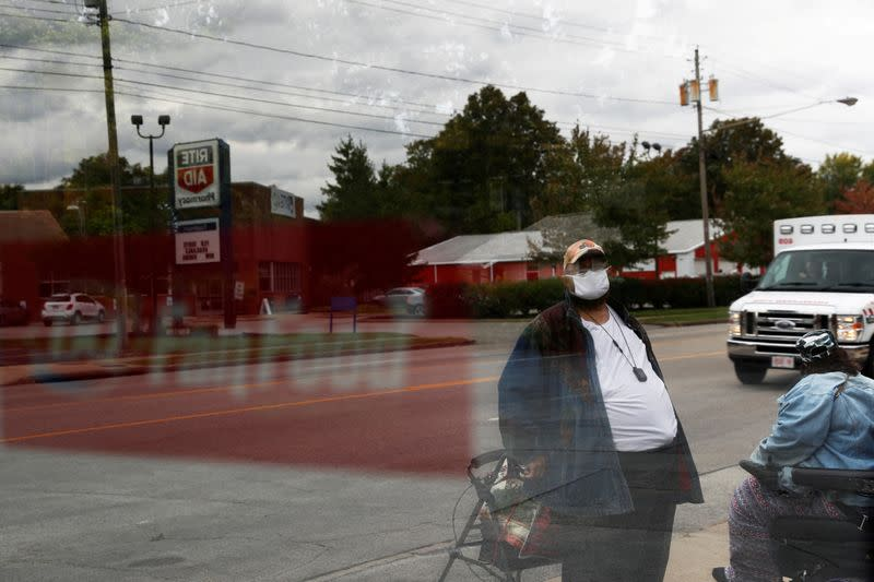 FILE PHOTO: A man is seen wearing a protective face mask reflected in a bus stop window in Warren, Ohio